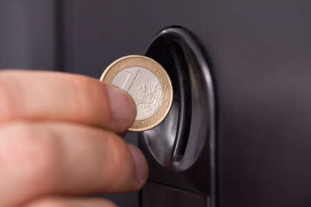 vending: Close-up of human hand inserting coin in vending machine