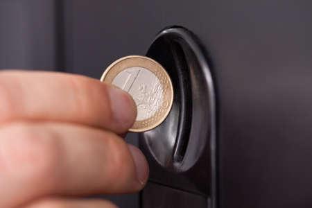 Primer plano de la mano del hombre que inserta la moneda en la máquina expendedora Foto de archivo