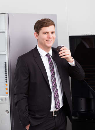 Portrait of happy businessman drinking coffee standing near vending machine photo