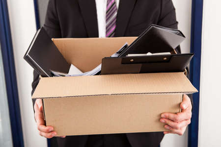 belonging: Portrait of young businessman holding cardboard in office Stock Photo