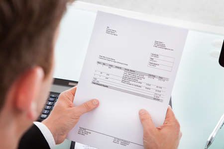 Portrait of a business man looking at invoice paper photo
