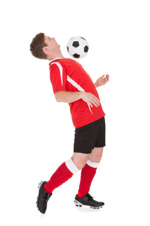 Soccer Player Playing With Ball Over White Background Standard-Bild