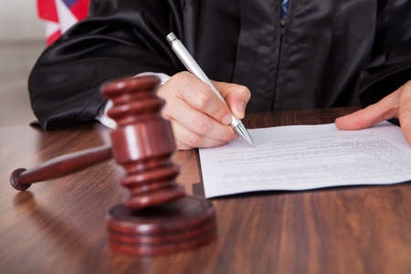 the litigation: Close-up Of Male Judge  Writing On Paper In Courtroom