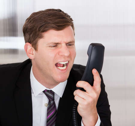 Portrait of angry businessman shouting on telephone in office photo