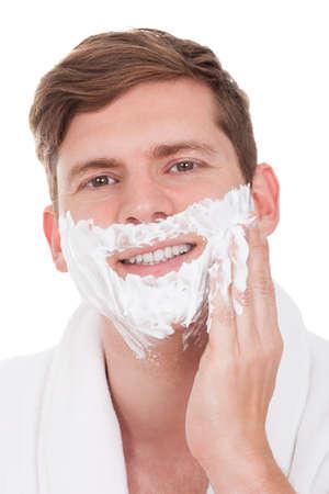 Happy Young Man Applying Shaving Cream Isolated On White Background photo
