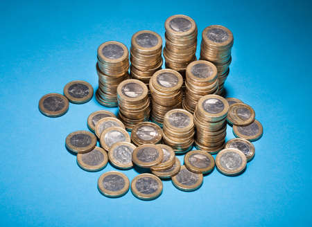 Stack Of Golden Coin Over Blue Background photo