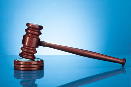proceedings: Wooden Gavel Resting On Block Over Blue Background
