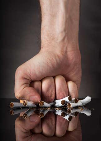 persona fumando: Primer Plano De Puño del hombre aplastamiento Cigarrillos Sobre Fondo Negro Foto de archivo