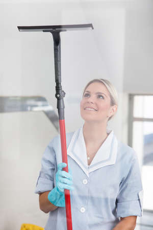 cleaning floor: Happy Woman Cleaning Glass With Rubber Window Cleaner