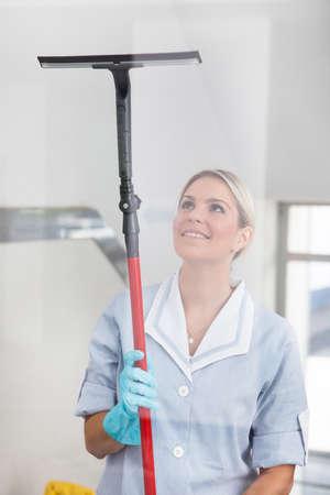 mujer limpiando: Mujer feliz de Vidrio Con Caucho Window Cleaner