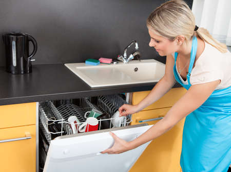 Woman Opening Dishwashers Door In The Kitchen photo