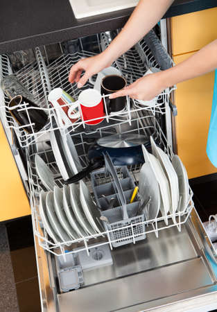 Happy Woman Putting Utensils In Dishwasher For Cleaning Stock Photo - 21253882