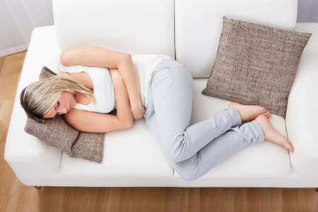 digestion: Portrait of woman with stomach ache sitting sofa Stock Photo