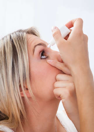 glaucoma: Close up young woman pouring drops in her eyes on white background Stock Photo