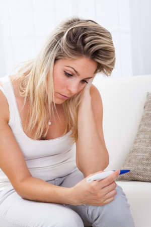 contraception: Worried young female checking pregnancy test at home