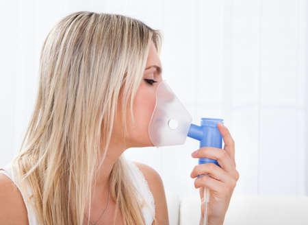 asma: Mujer con asma usando un inhalador para el asma para prevenir los ataques Foto de archivo