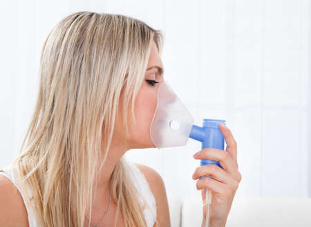 bronchitis: Woman with asthma using an asthma inhaler for preventing attacks