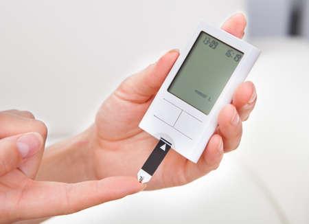 blood pressure monitor: Close-up Of Hand Holding Sugar Level Checking Machine