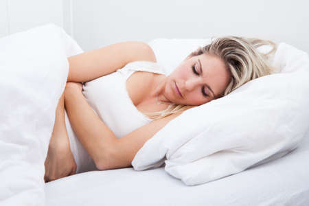 Portrait of woman with stomach ache lying on bed photo