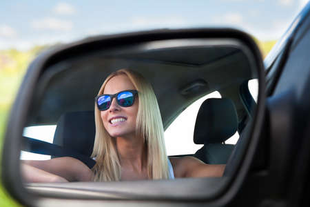 mirror face: Young Blonde Woman Wearing Sunglasses Driving Car Stock Photo