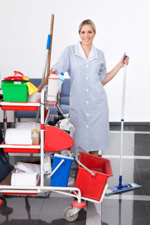 Young Happy Maid Cleaning The Floor With Mop photo