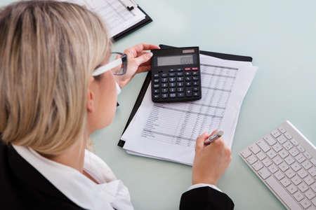 calculadora: Joven Empresaria C�lculo de datos En Su Oficina