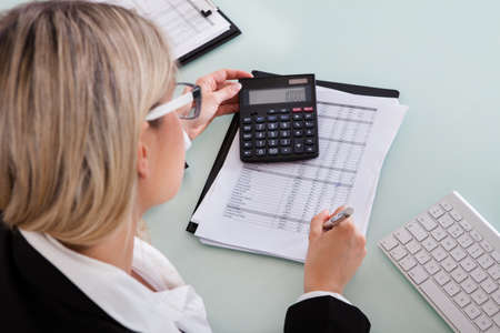 Young Businesswoman Calculating Data In Her Office Stock Photo - 21235196