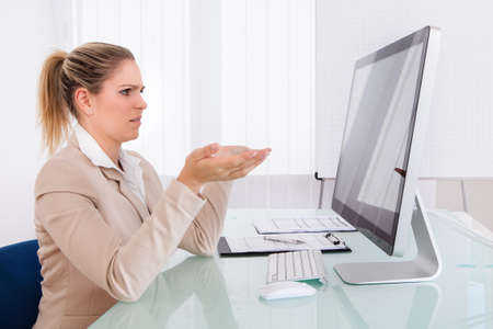 Businesswoman Looking At Computer Gesturing At Workplace photo