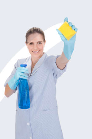 Woman Holding Cleaning Liquid And Scrubber Over White Background photo