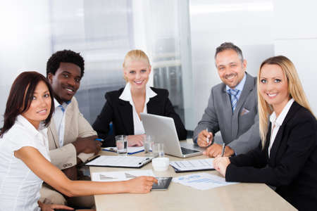 CONFERENCE TABLE: Group Of Multi Ethnic Businesspeople Discussing Together In Office