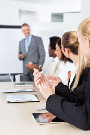 appreciating: Business People Appreciating Businessman Explaining In Presentation Stock Photo