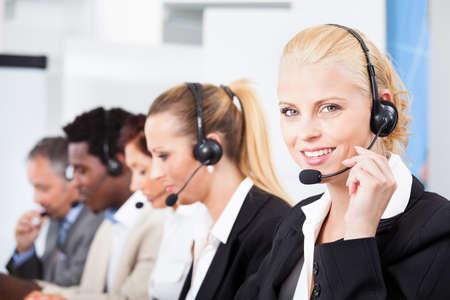 Happy Co-travailleurs portant des écouteurs fonctionnant au centre d'appels