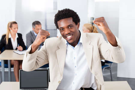 Portrait Of Successful African Businessman Sitting In Front Of Colleagues photo
