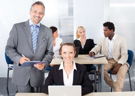 Businessman Standing Beside Businesswoman Looking At Laptop photo