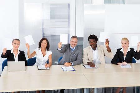 jurado: Grupo de felices Funcionarios de Recursos Humanos Corporativos sostiene el papel en blanco Foto de archivo