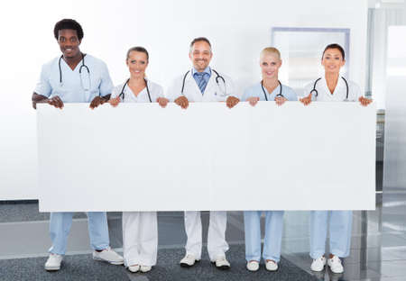 Group Of Happy Multiracial Doctors Holding Placard In Clinic photo