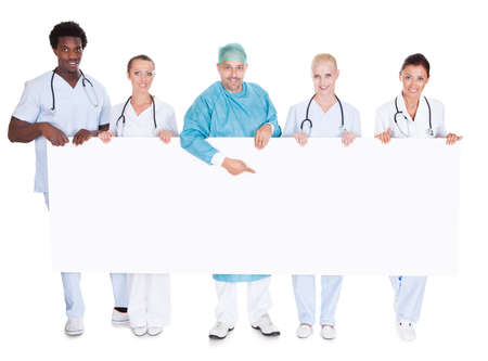 Group Of Multiracial Doctors Holding Placard Over White Background photo