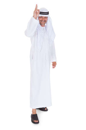 Portrait Of Mature Islamic Man Gesturing Over White Background photo