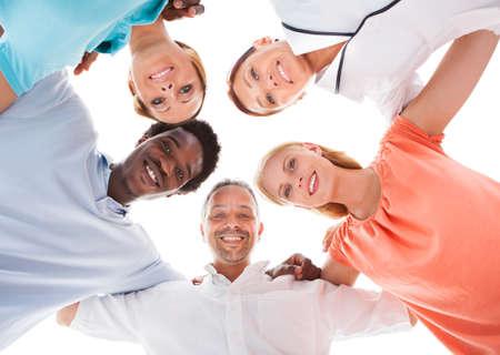 ležérní: Šťastné skupina lidí s vedoucí dohromady více než bílé pozadí