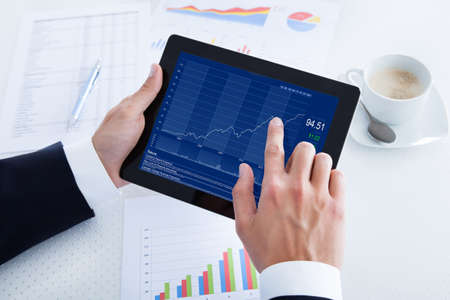Businessman Analyzing Graph On Digital Tablet In Office Stock Photo - 21254149