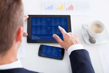 Businessman Analyzing Graph On Digital Tablet In Office Stock Photo - 21254172