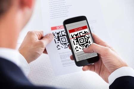 codigos de barra: Primer plano del hombre de negocios de escaneo de código de barras usa el teléfono celular