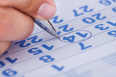 entry numbers: Close-up Of Man Highlighting Date On Calendar