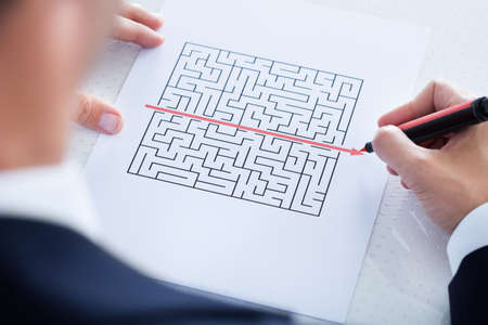 maze game: Businessman Solving Maze Puzzle With Red Pen Stock Photo