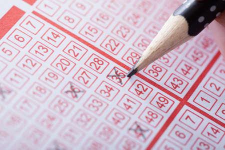 loteria: Primer plano de una persona Marcado Número On billete de lotería con el lápiz