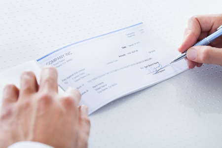payroll: A Male Hand Filling Out The Amount On A Cheque