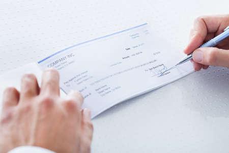 Un homme part en remplissant le montant sur un chèque Banque d'images - 21254253