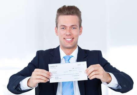 držení: Portrét mladého šťastný podnikatele nabízející Šek