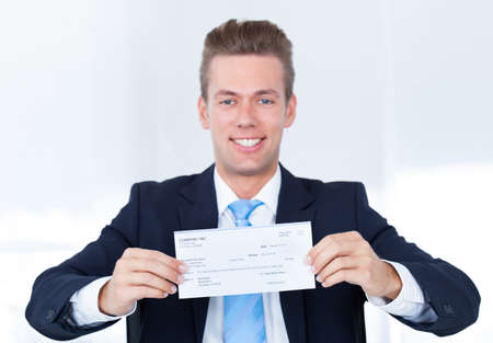 cheque: Portrait Of Young Happy Businessman Offering Cheque Stock Photo