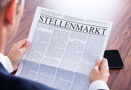 periodicos: Peri�dico de la lectura del hombre de negocios con el Stellenmarkt Headline Foto de archivo